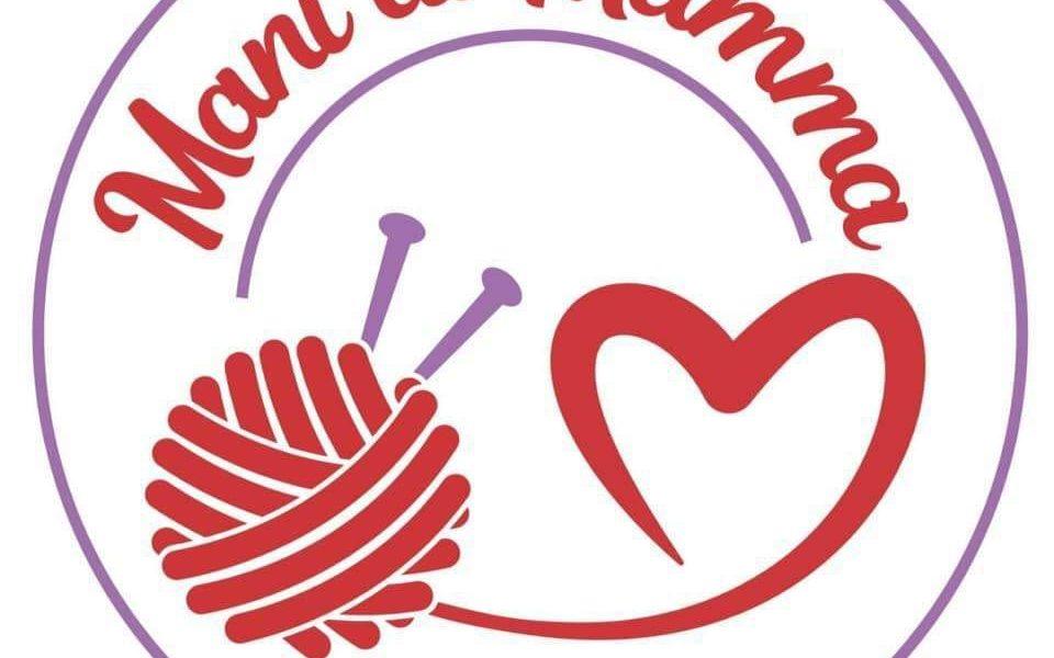 Mani di mamma: il logo di un cuore rosso, un gomitolo rosso e dei ferri per lana