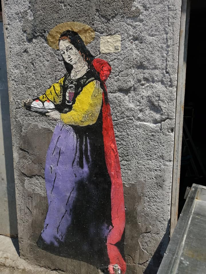 Aureola, il piatto con le minnuzze, strappatele da Quinziano, ricchi abiti dai colori vivi che rimandano al sacrificio, al martirio, alla consacrazione verginale a Dio, la collana e lo stemma del Calcio Catania nel petto, questa è la Sant'Agata proposta da Tvboy.