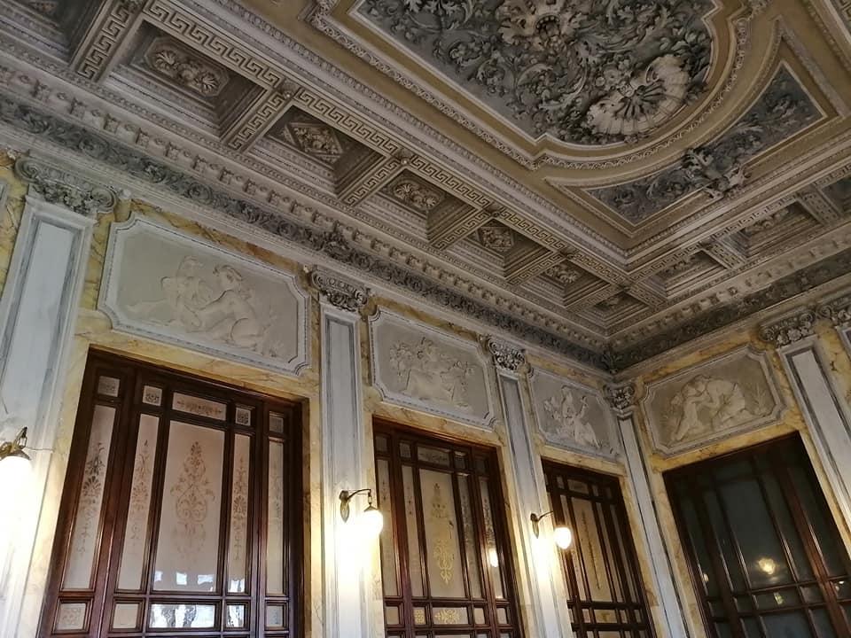 Lo scalone che dà accesso al palazzo Libertini Scuderi presenta di tre rampe ed è riccamente decorato in stile neoclassico-rinascimentale.