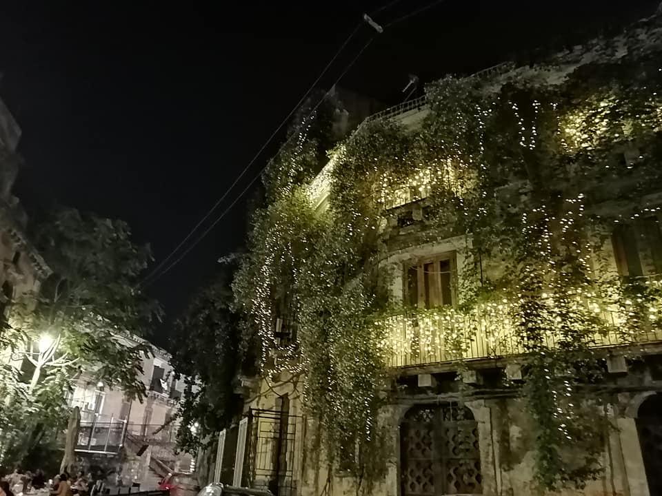 La caratteristica forma di Palazzo Stidda a forma di nave, abbellita da piante e luci.