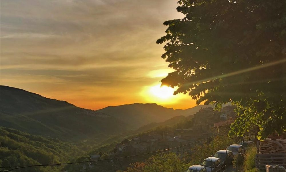 il sole che scende dietro le montagne dipingendo il cielo di giallo e arancione
