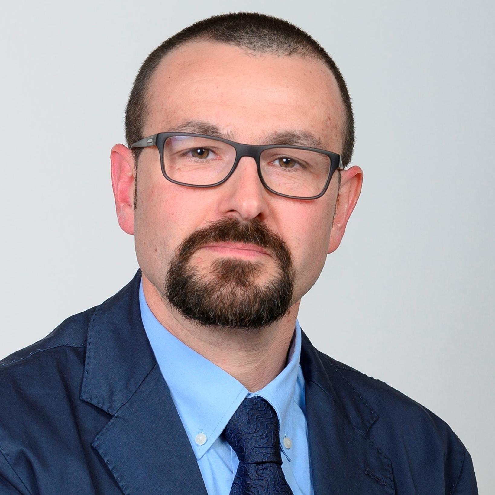 Gianfranco vestito con abito e cravatta blu e occhiali neri