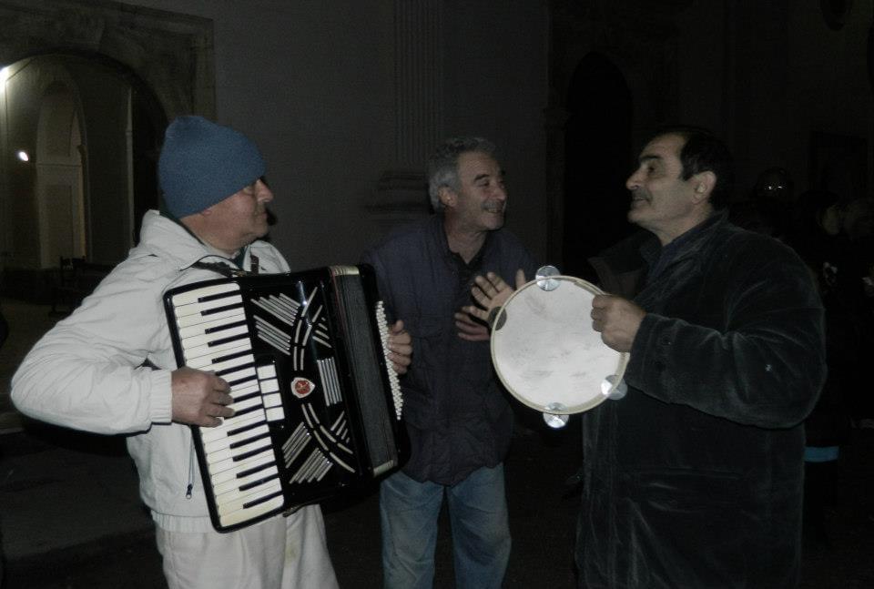tre uomini che cantano a suon di tamburello e fisarmonica