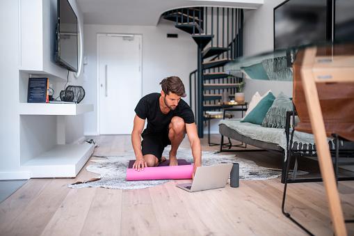Fitness e pandemia - Ragazzo si allena in casa seguendo degli allenamenti online durante la pandemia