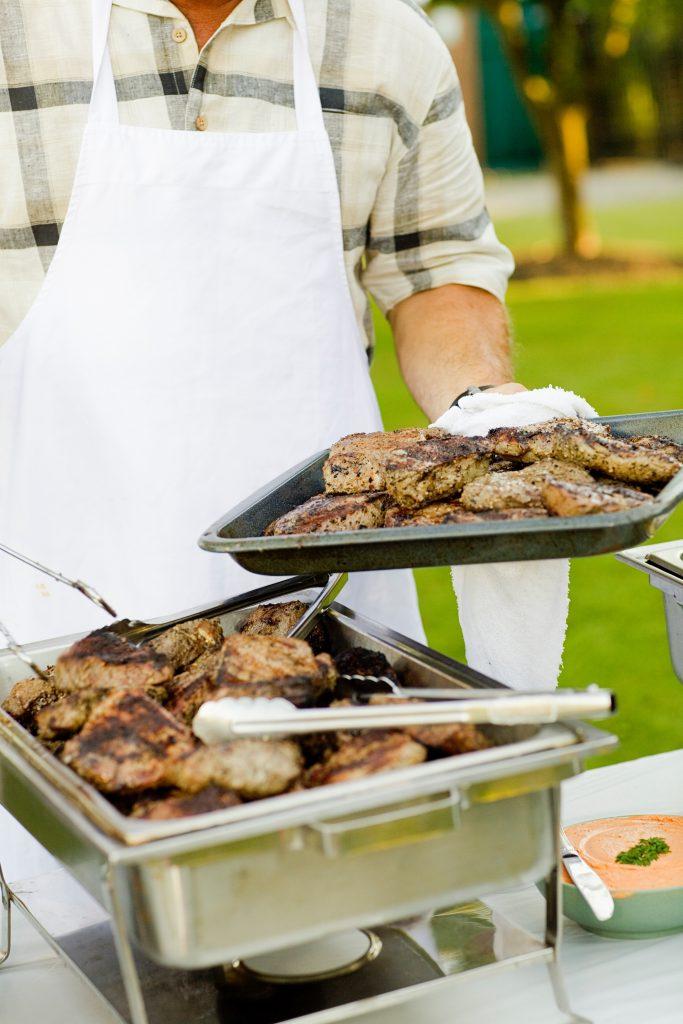 due vassoi di carne grigliata e uomo con grambiule