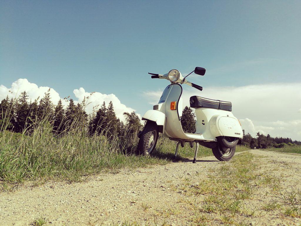immagine di una moto, Vespa ferma in una strada sterrata
