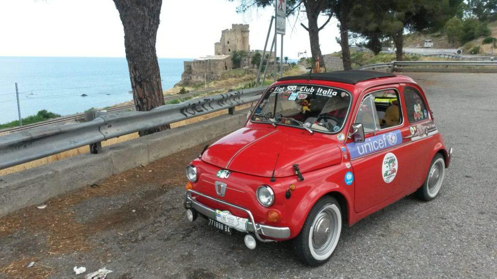 una 500 rossa parcheggiata vicino al mare