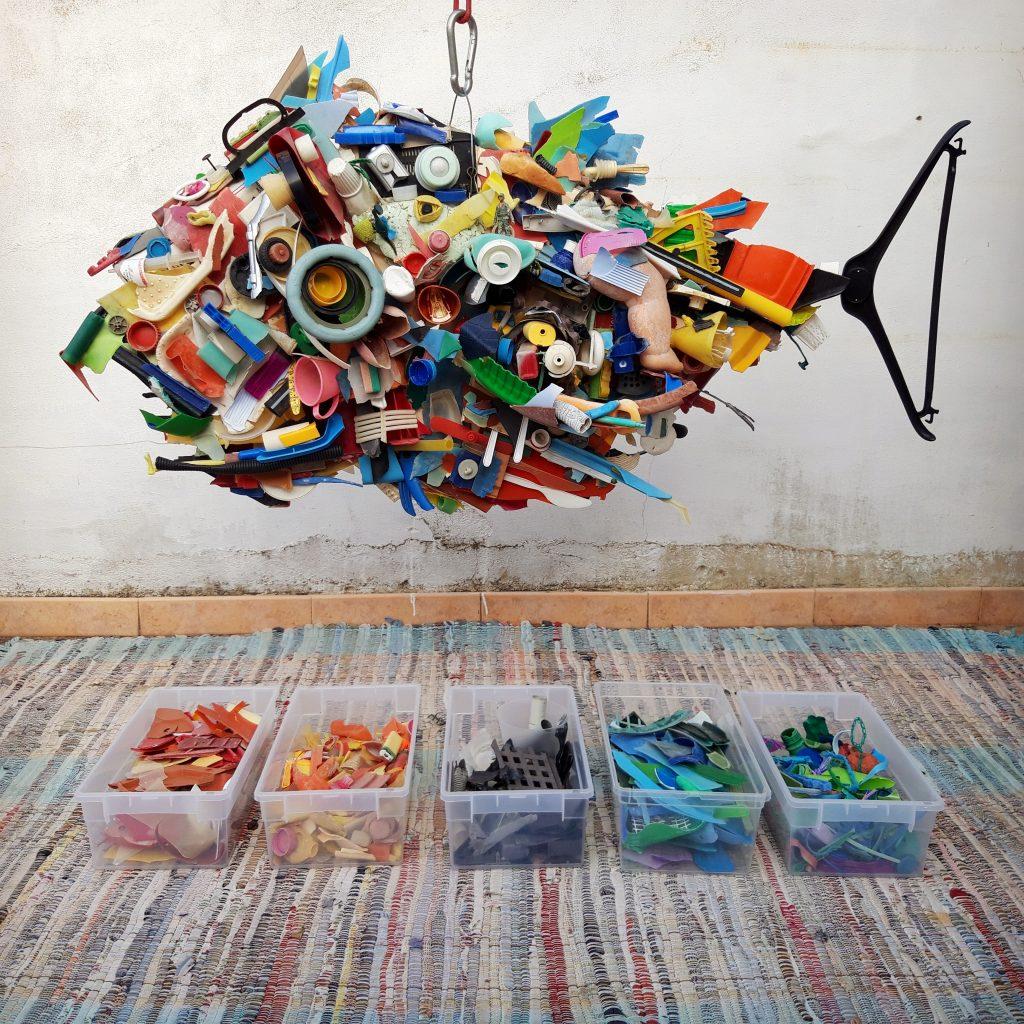 pezzi di plastica assemblati a forma di pesce appeso ad un amo