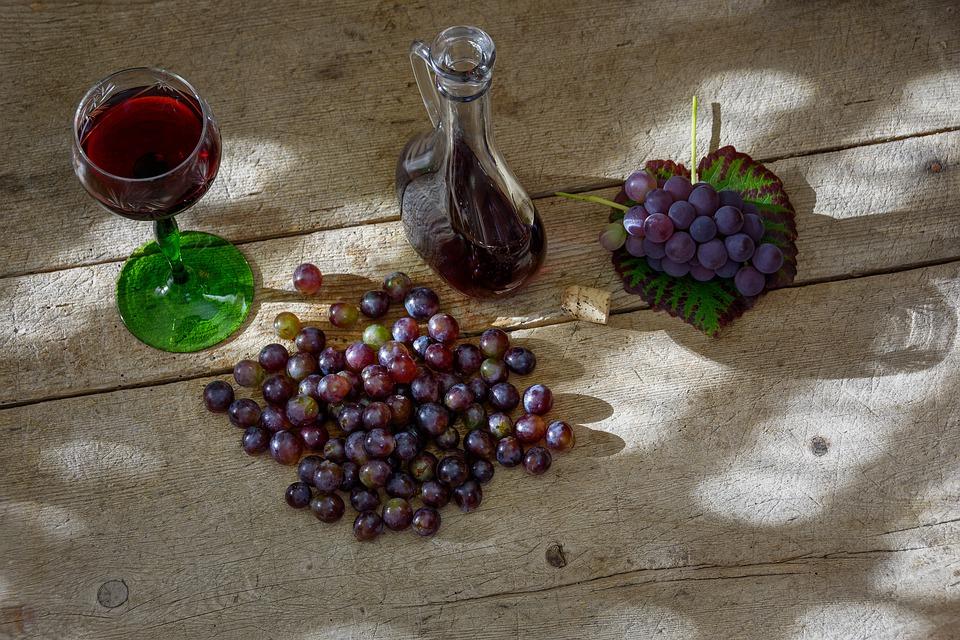 Vino Nuovo con i grappoli di uva su un tavolo