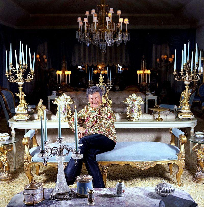 Liberace seduto su una lunga panca celeste circondato da candelabri