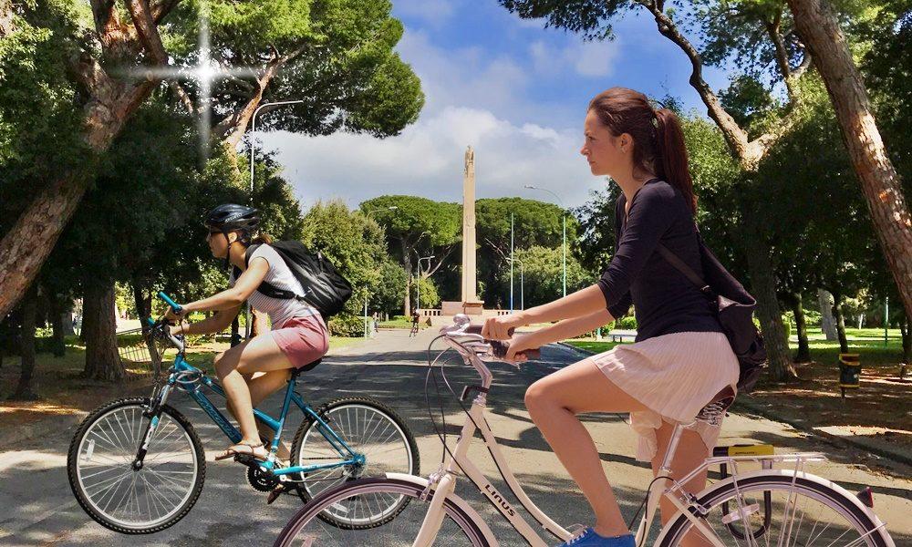 Biciclette e monopattini - ragazze in bici lungo il viale