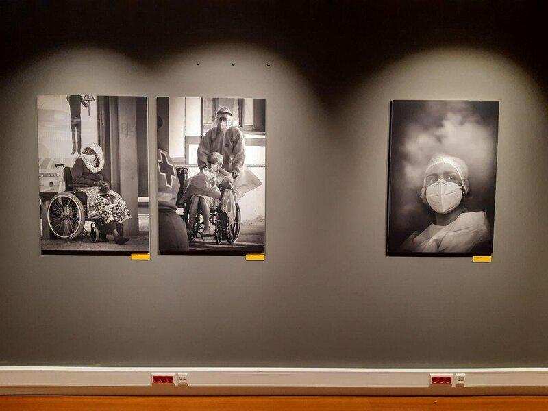 Quadri in bianco e nero realizzati da Alfredo Cunha appesi ad una parete bianca. I soggetti sono su una sedia a rotella e indossano le mascherine