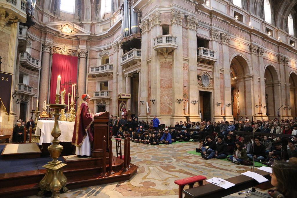 Basilica Interna Palazzo Di Mafra. Un panno rosso , dei candelieri, il Patriarca che celebra la messa con tanta gente seduta ad ascoltare