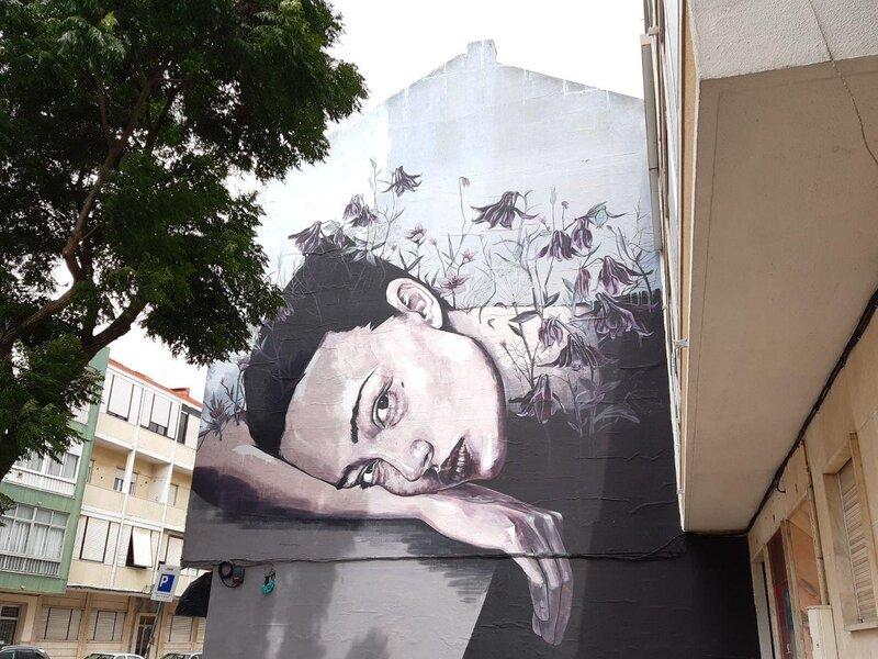 Le fronde di un albero con accanto un murales che rappresenta Ofelia, personaggio di Shakeaspeare, in una versione contemporanea