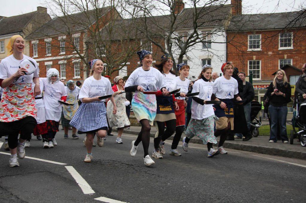Englishpancakerace nel Pancake Day 2019 - donne che corrono con padella con dentro i pancake