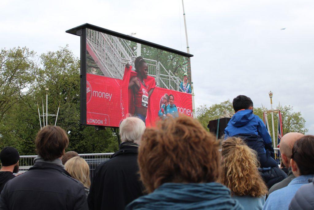 Maratona di londra: folla davanti a uno schermo guarda la vincitrice Brigid Kosgei dopo l'arrivo al traguardo