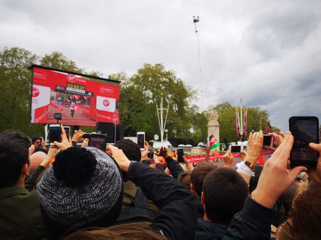 Maratona di londra -Folla davanti a uno schermo guarda il vincitore Eliud Kipchoge tagliare il traguardo