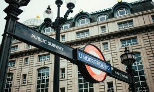 ingresso della metro segnalato dalla scritta underground su sfondo blu che taglia orizzontalmente un cerchio rosso e bianco