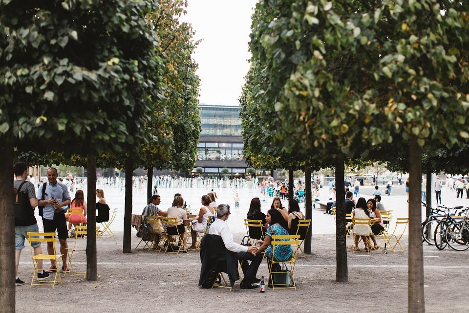 Giovani Italiani - ambiente aperto con alberi laterali e persone che socializzano seduti su sedie gialle
