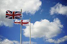 Tornare in Italia: due Bandiere in un palo con cielo nello sfondo