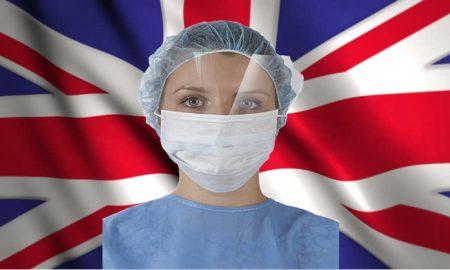 Mercoledì Londra è zona rossa - Mascherina su operatrice sanitaria in Union Jack