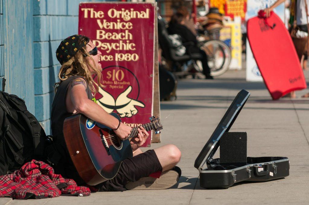 Venezia - Immagine di un chitarrista seduto per terra si esibisce in una via di Venice beach