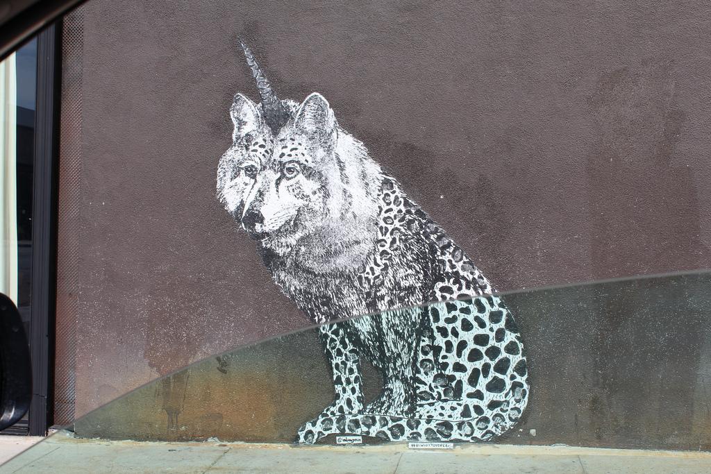 Street art - murales rappresentativo di uno strano animale con muso da lupo e corpo da felino