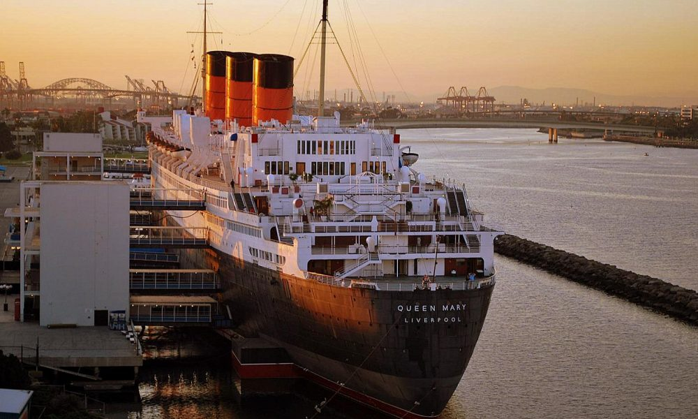Queen Mary. Transatlantico armeggiato a Long Beach nei colori nero, bianco e erancione sotto un cielo al tramonto