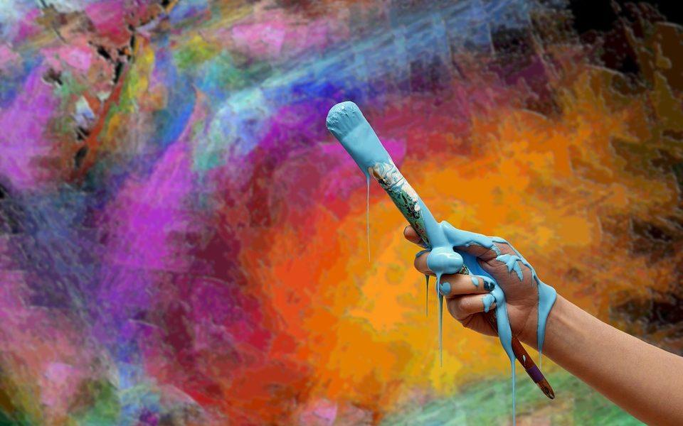 Street art - un muro variopinto fa da sfondo alla mano dell'artistista che impugna un pennello zuppo di azzurro