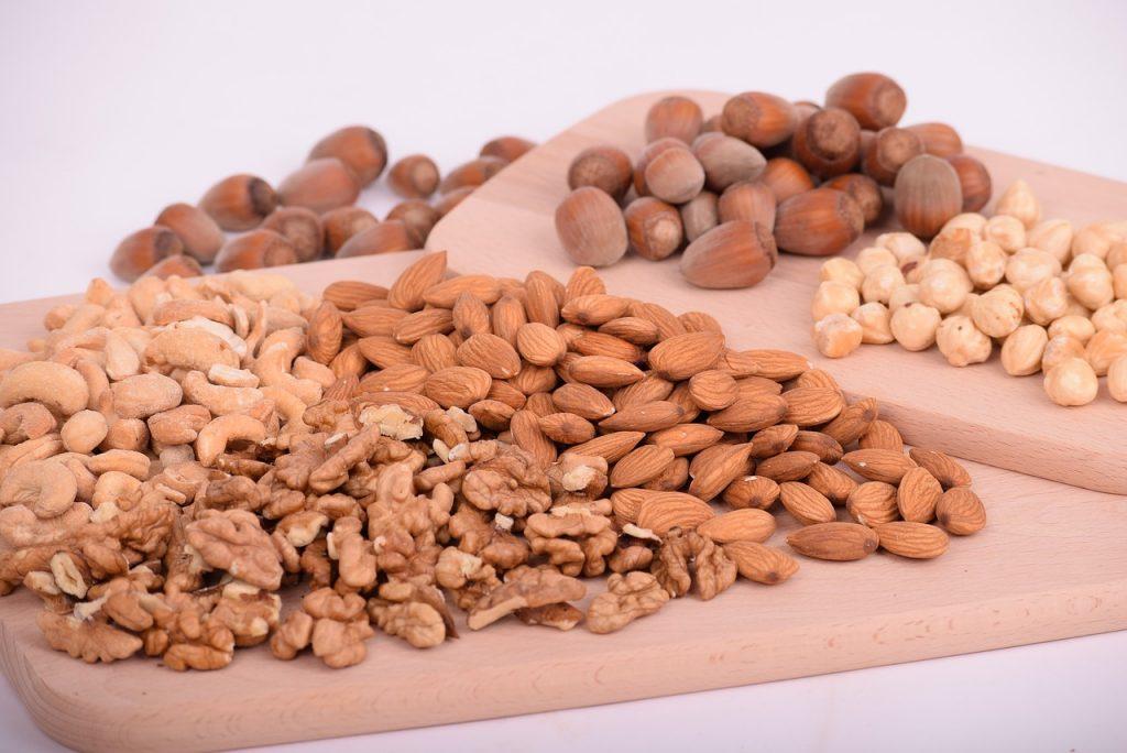 Nocciole - Tagliere di legno sopra il quale ci sono nocciole, mandorle e noci