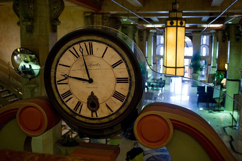 Hotel Cecil - In primo piano un grande orologio con numeri romani e struttura in legno collocato nella Hall dell'hotel Cecil