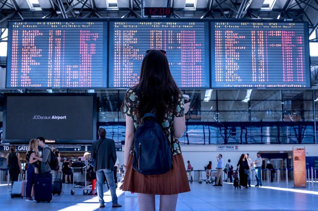 volare con cani e gatti dall'Italia a Los Angeles -ragazza all'aeroporto davanti al tabellone