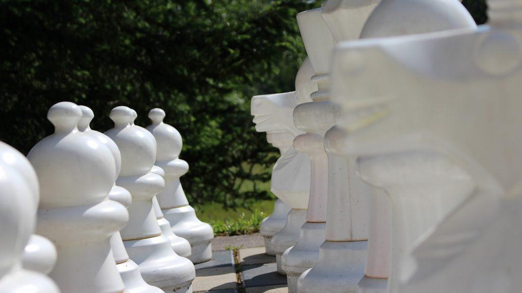 Santa Monica. Scacchiera in primo piano con giganti scacchi di colore bianco è poggiata su di un prato