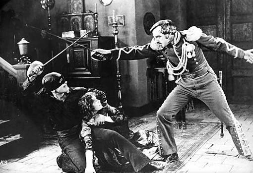 Zorro di LA inginocchiato stringe a sè una fanciulla mentre con l'altra mano sguani la spada per difendersi da un nobil uomo