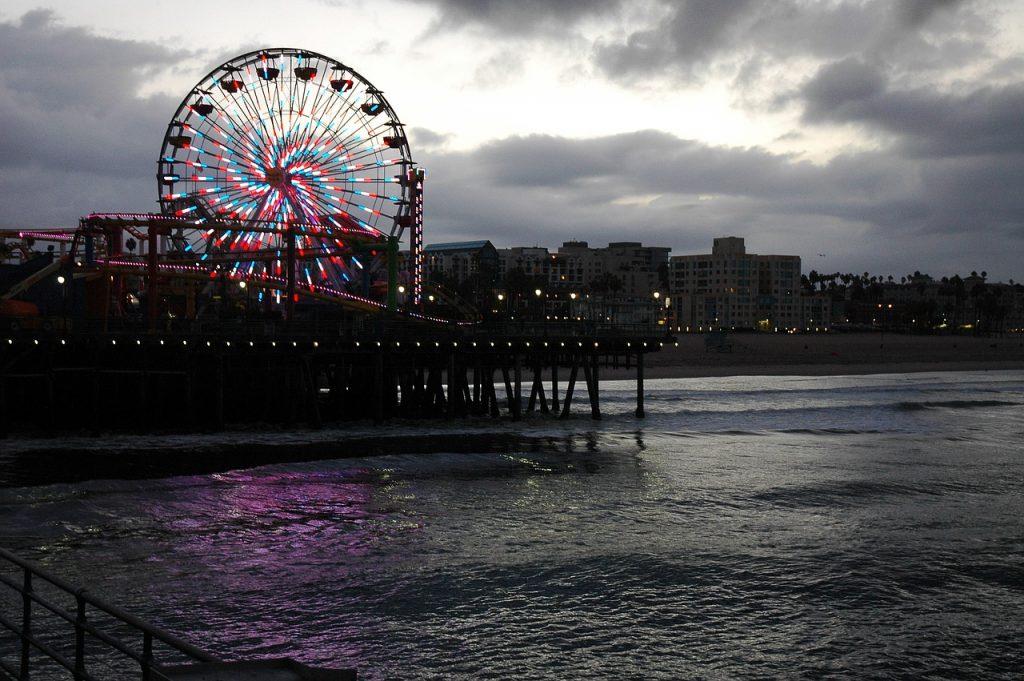 Santa Monica. La colorata ruota panoramica si affaccia sulle sfumature di un cielo e di un mare grigio lungo il molo di S. Monica