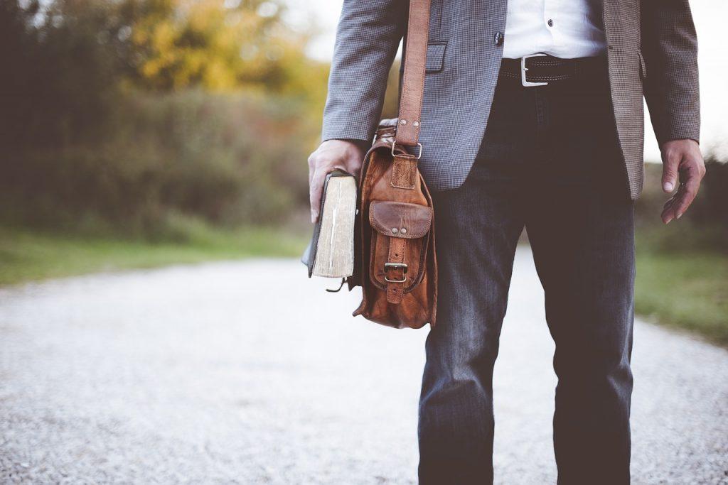 Leo Buscaglia. Immagine di un insegnante di cui si vedono gli strumenti da lavoro: libro e valigetta