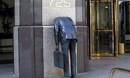 Businessman. Scultura dell'uomo d'affari con testa dentro la parete di un grattacielo