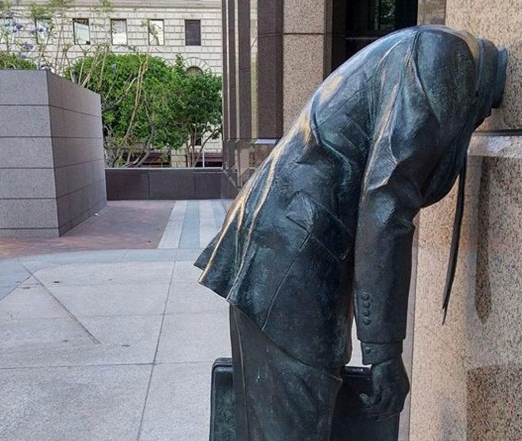 Businessman. La scultura dell'uomo d'affari di LA con testa infilata nel muro dell'Ernst and Young
