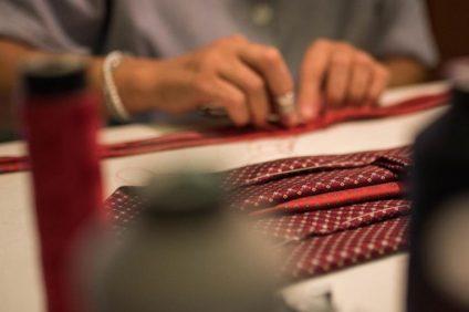 Mani di sarta a lavoro alla E. Marinella