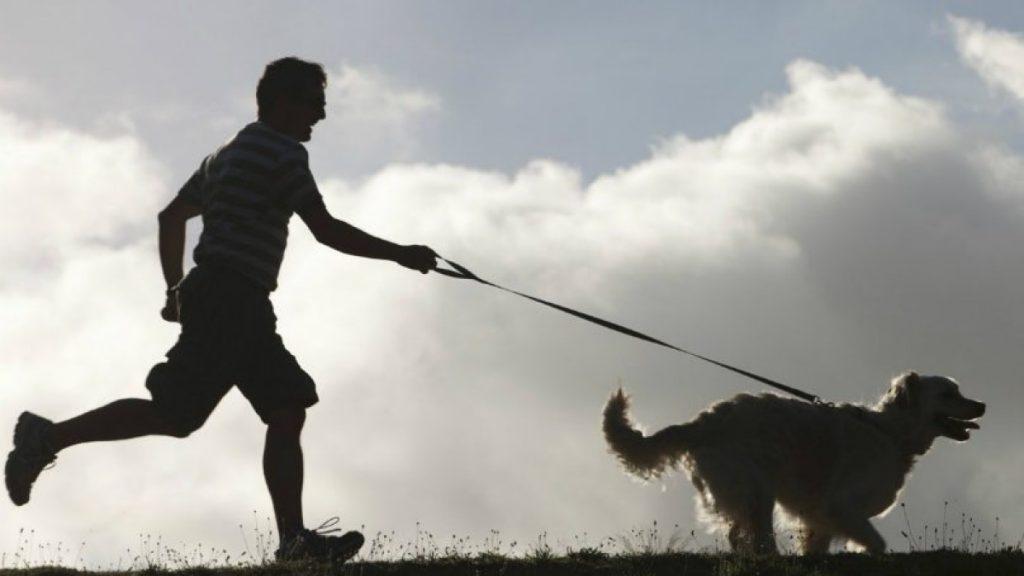 Uomo corre con un cane