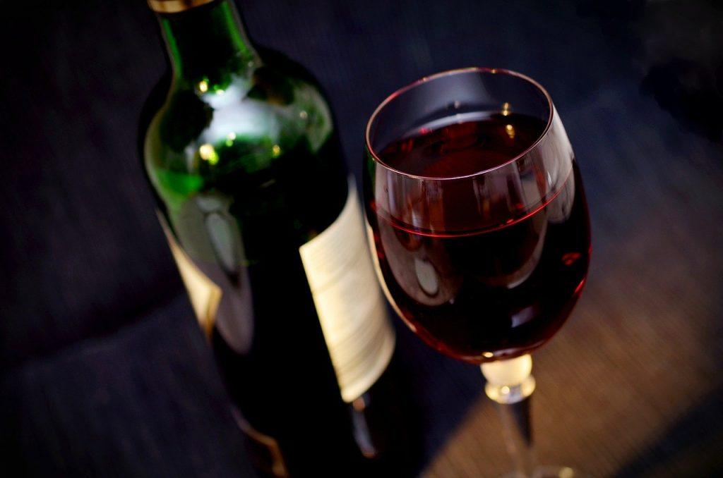 Vino rosso in calice con bottiglia