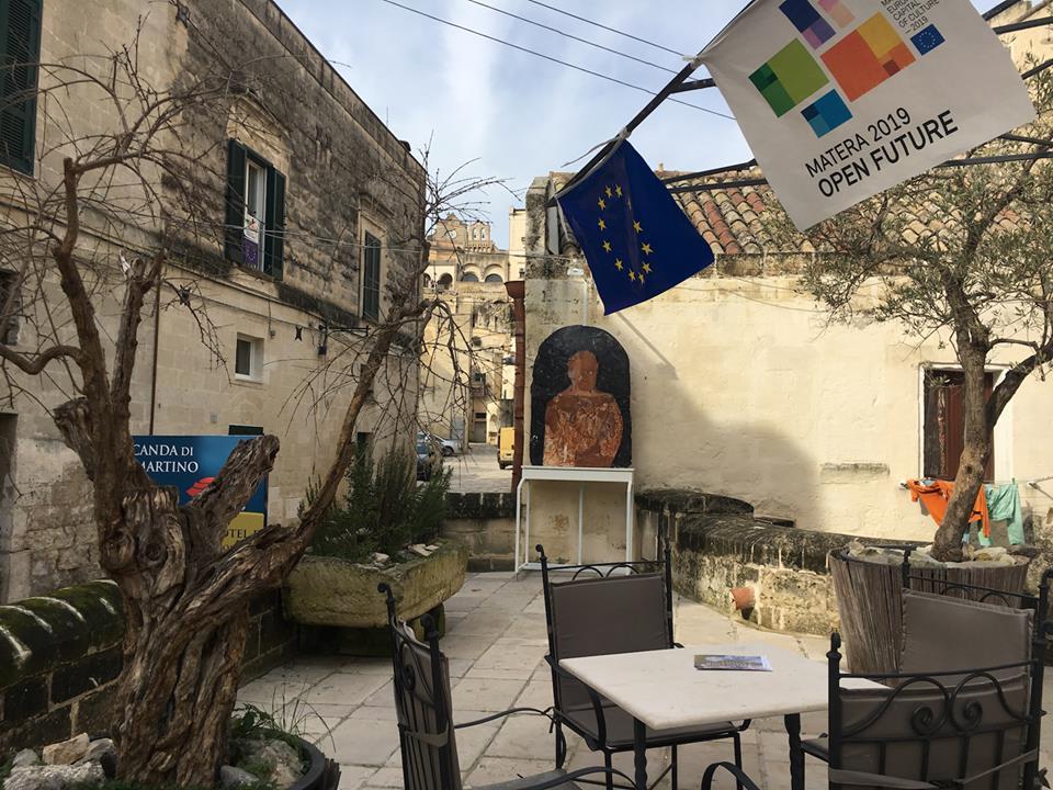 la piazza di un borgo antico di Matera con sedie e tavolino