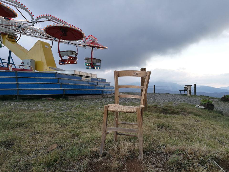 una sedia e una giostra in una campagna desolata