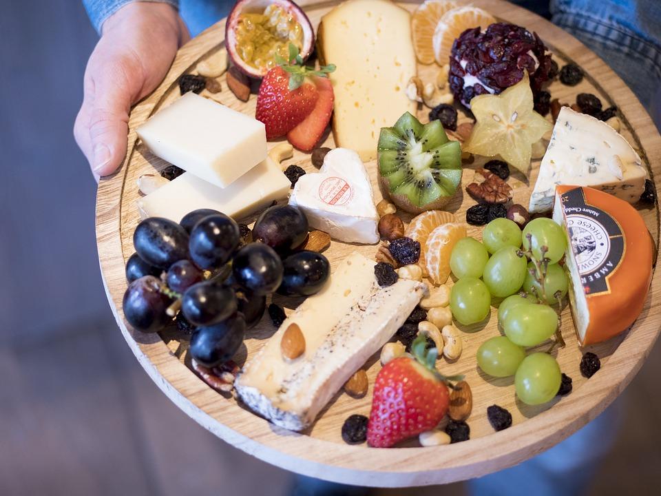 un tagliere con tanti prodotti tipici della cucina italiana come formaggi e frutta