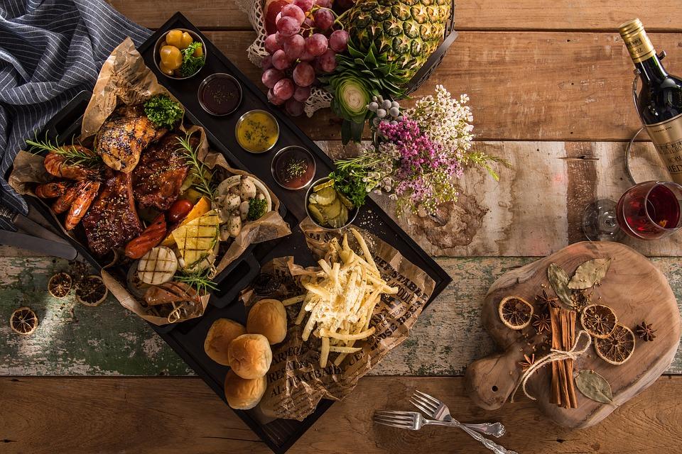 tavola imbandita con frutta, carne, ortaggi e vino