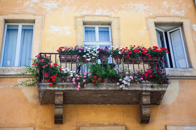 Fiori su un balcone di una casa antica come sarà a Palazzolo