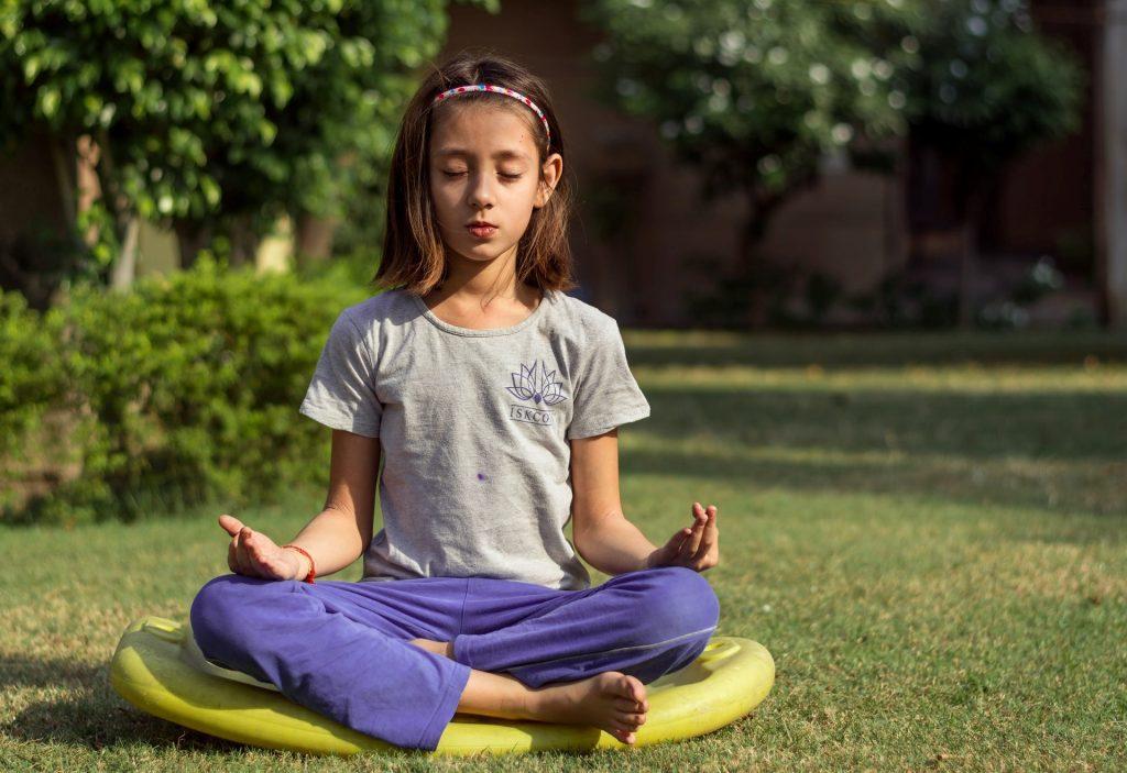 Bambini  - una bambina seduta sull'erba che fa yoga