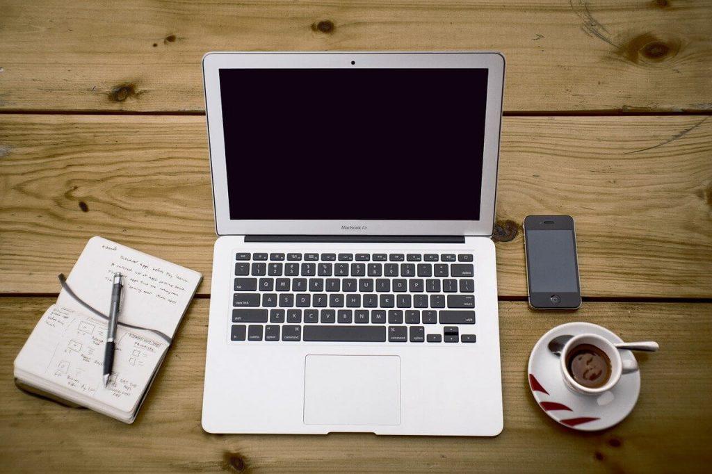 Micro-entreprise - un pc sul tavolo con accanto un telefonino e una tazza di caffè