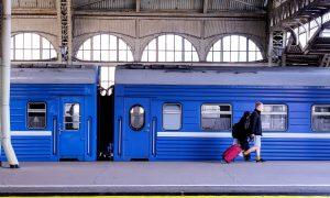 Train Bleu - viaggiatore con trolley rosso accanto ad un treno blu