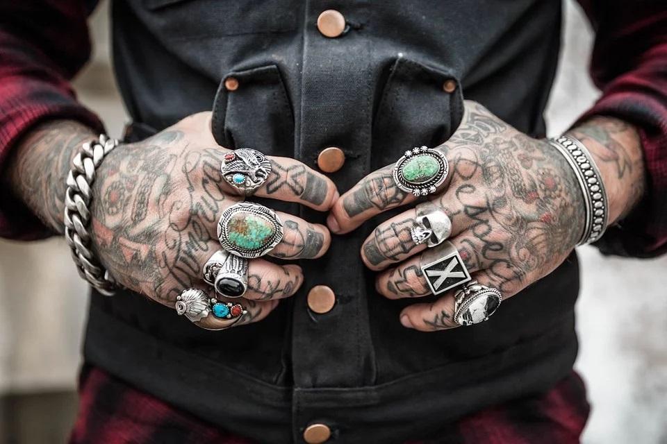 Tattoo convention con le mani di un uomo tutte tatuate